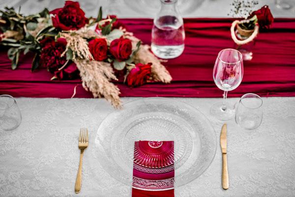 Trouwlocatie Diner tafel ingedekt met glazen bord en rood thema